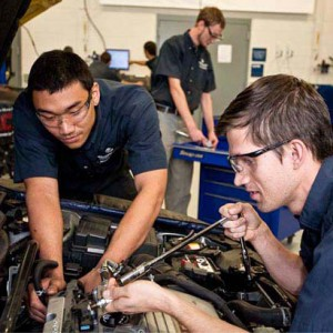 two young men working on a car engine