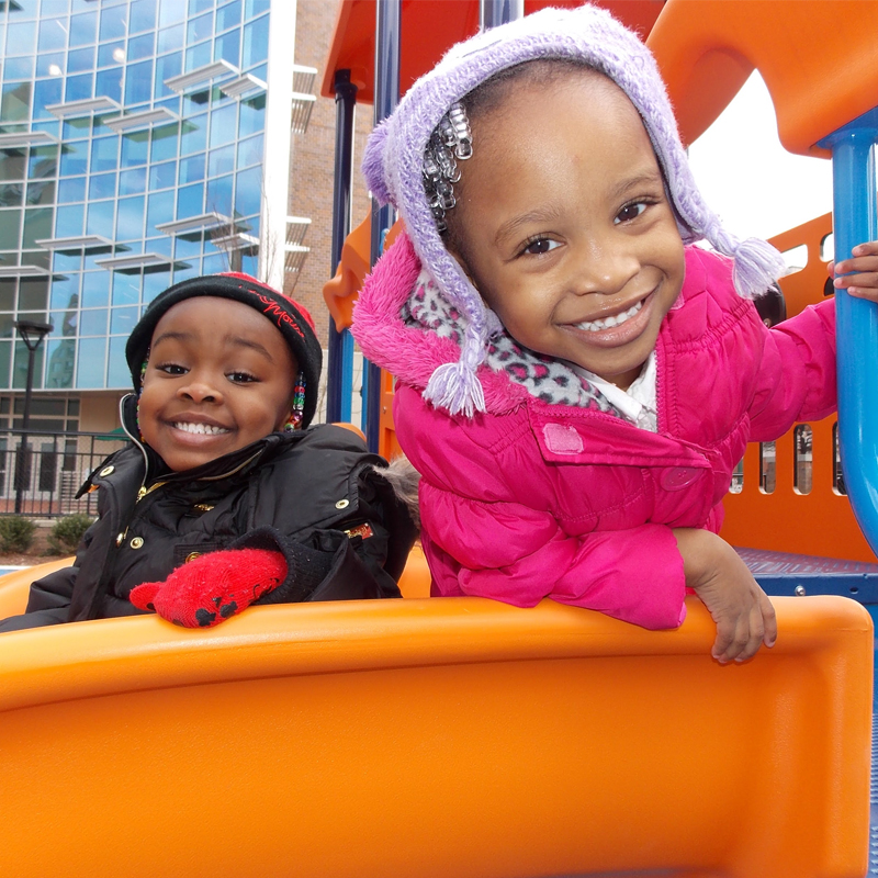 2 children playing at a park on TCC Norfolk Campus