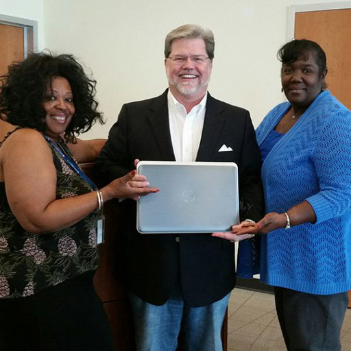 smiling man holding a laptop flanked by two smiling women