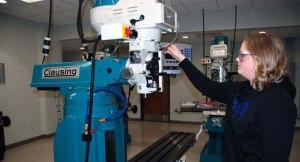 female student using machining instrument